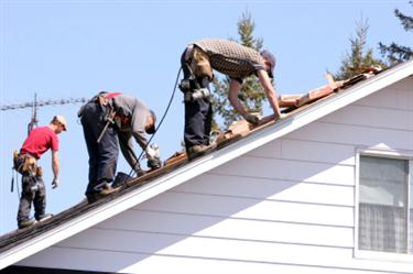 Roof Installation in Barhamsville VA. Three roofers laying new shingle on a roof in Barhamsville.